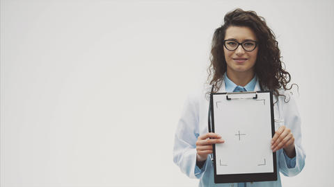 Smiling female doctor with a folder in a single standing.... Stock Video Footage