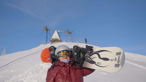 Senior woman holding snowboard on shoulder and looking around on snowy slope Live Action