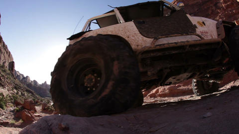 Jeep drives up bump, focal point on back tire Footage