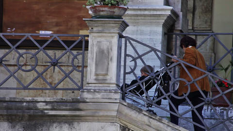 A woman carefully brings a stroller holding a child down some stairs in Rome, It Footage