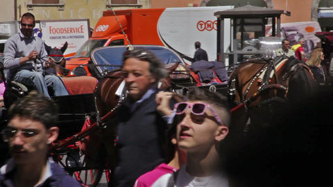 A horse and buggy pull up on a busy street filled with people and cars in Rome,  Footage