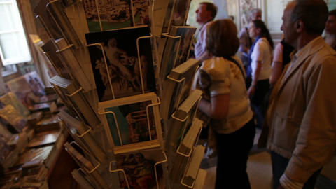 Footage of a postcard display in a Vatican Museum gift shop and the tourists in  Footage