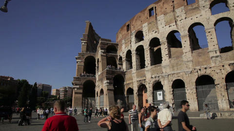 Tourists roam the exterior of the Colosseum on a sunny day in Rome, Italy Footage