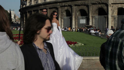 A newly married couple poses for pictures outside the Colosseum in Rome, Italy Footage