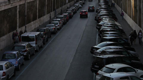 Cars driving down a narrow street with cars parked along both sides Footage