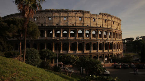 Colosseum and cars driving by seen from nearby park Footage