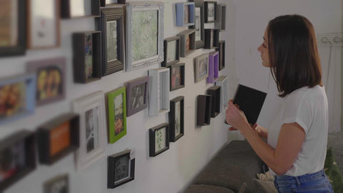 Young woman decorates her living room at home Footage