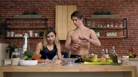 Handsome fit woman making note in note book while beautiful young man taking jar Footage