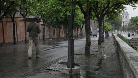 Man walking down a windy street in Rome Footage