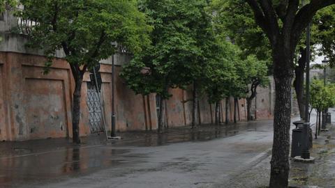 Car passes through an empty wet street Footage