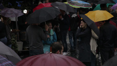Strangers talk in a umbrella filled crowd Footage