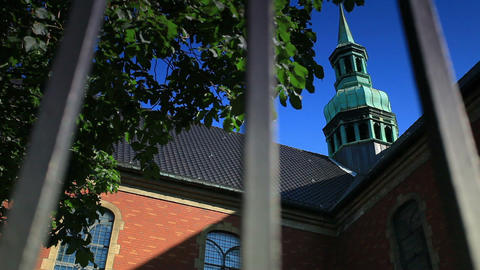 Tracking shot of a church steeple through a fence in Copenhagen, Denmark Footage