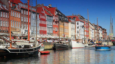 Static shot of colorful buildings and people on street and ferry boat in Copenha Footage