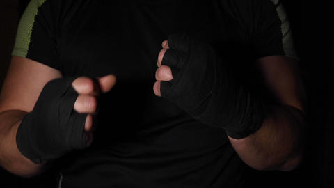 athlete is standing in a boxing rack, his hands are wrapped in a black bandage Footage