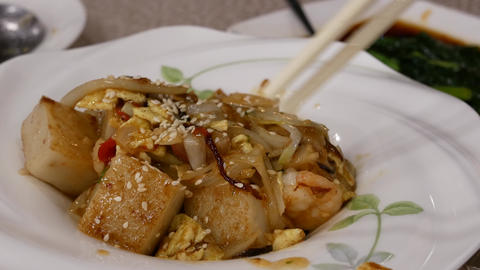 Motion of people eating pan fried turnip cake dim sum inside Chinese restaurant Footage