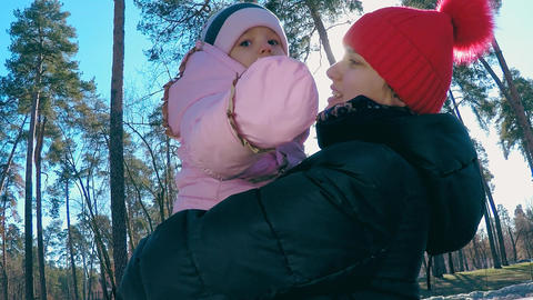Mom holds her daughter in her arms against the backdrop of sunlight in the park Footage