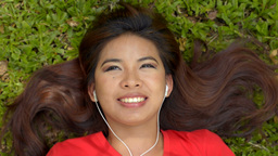 Woman Lying on the Grass Listening to Music on her Headphones Footage