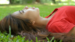 Young Woman Relaxing, Lying on the Grass in a Park Footage