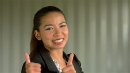 Young Asian Businesswoman Giving a Smiling Thumbs Up to the Camera Footage