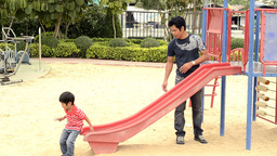 Father and Son Playing on a Slide Stock Video Footage