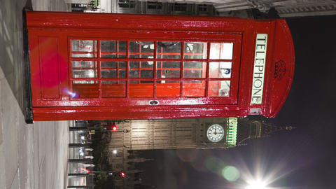Vertical shot of Tracking time-lapse of Big Ben behind a telephone booth in Lond Footage