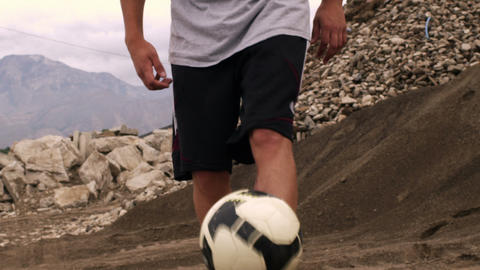 Close up of someone juggling a soccer ball in the dirt Footage