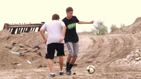 Boys playing soccer in the dirt Footage