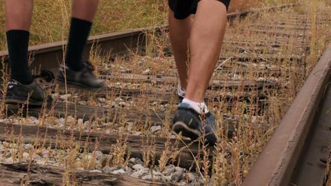 Two boys walking down abandoned railroad tracks Footage