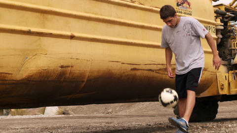 Juggling a soccer ball in front of a large tractor Footage