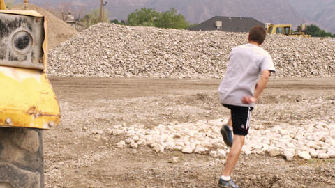Boy doing soccer moves in an excavation quarry Footage
