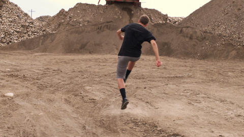 Boy running and kicking a soccer ball in the dirt Footage