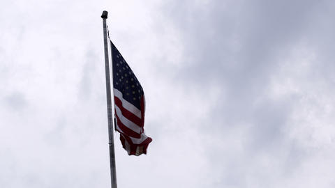 American flag waving in the sky with gray clouds in the background Footage