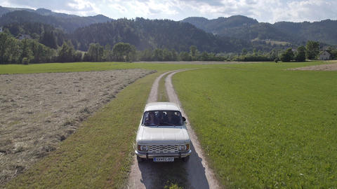 Aerial, front view - Old, white car driving on a field road Live Action