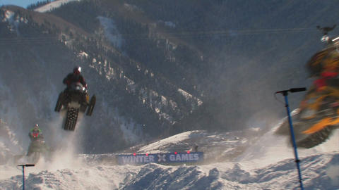 Snowmobile race with snowmobilers jumping Footage