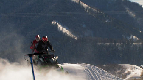 Jumping snowmobiles in a race Footage