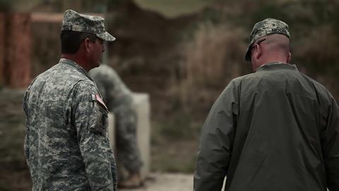 Range instructors talking at firing range Footage