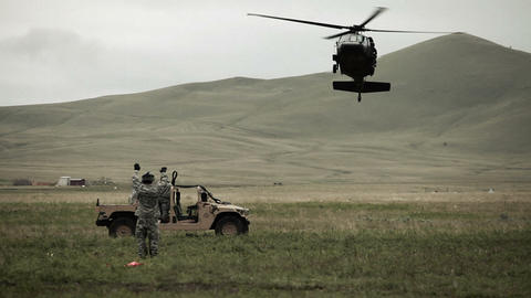 Shot from ground of Black Hawk helicopter approaching Humvee Footage