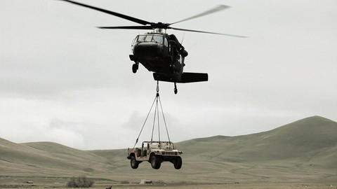 Shot from ground of Black Hawk helicopter lifting Humvee while soldier gives sig Footage
