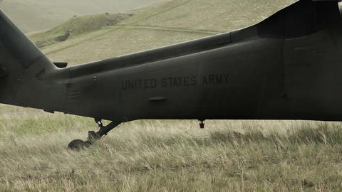 Shot from field of landed Black Hawk helicopter tail boom Footage