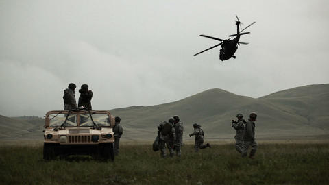 Shot of soldiers in Humvee while Black Hawk helicopter flies overhead Footage