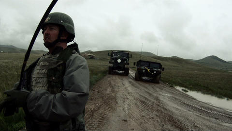 Shot from the back of a convoy vehicle soldier cleaning up Footage