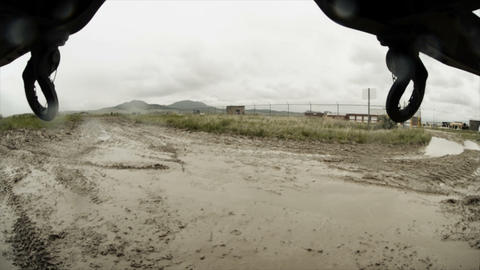 Shot from under vehicle in convoy training, driving in very muddy area Footage