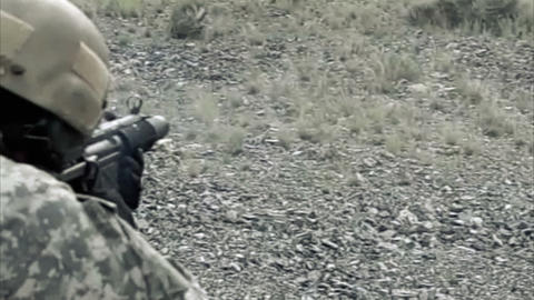 Static shot, soldier shooting automatic small target rifle at range while kneeli Footage
