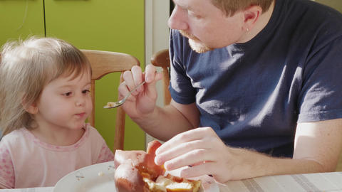 Father feeding child attracting attention to spoon at home ビデオ
