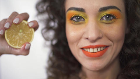 Close up portrait of young curly girl with bright make up squeezing sour lemon Footage