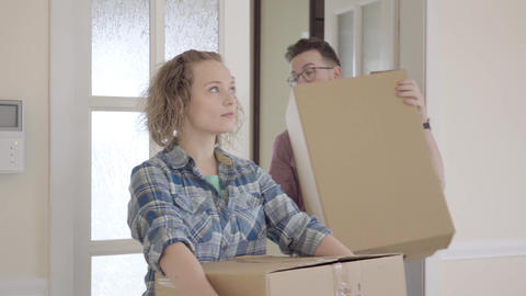 Joyful man and woman in casual dress with boxes in hands come to their new home Footage