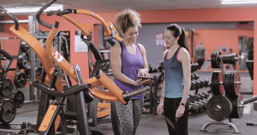Woman discussing workout progress with fitness instructor Footage