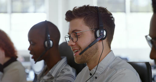 Side view of young cool mixed-race call center team calling and sitting at desk of modern office 4k Live Action
