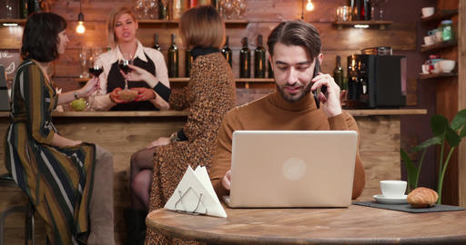 Young freelancer having a phone conversation in a busy restaurant Live Action