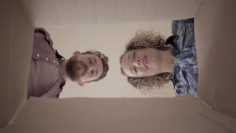 Bearded man and smiling woman lean over box and look... Stock Video Footage